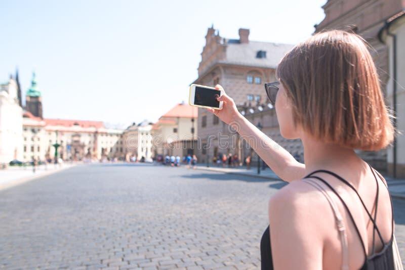 De vrouw loopt op een zonnige de zomerdag langs de straten van de oude stad en maakt een foto op een smartphone stock foto