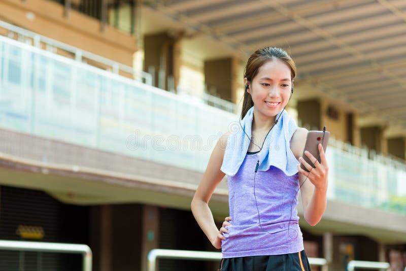 De vrouw luistert aan lied met mobiele telefoon in sportstadion stock afbeelding