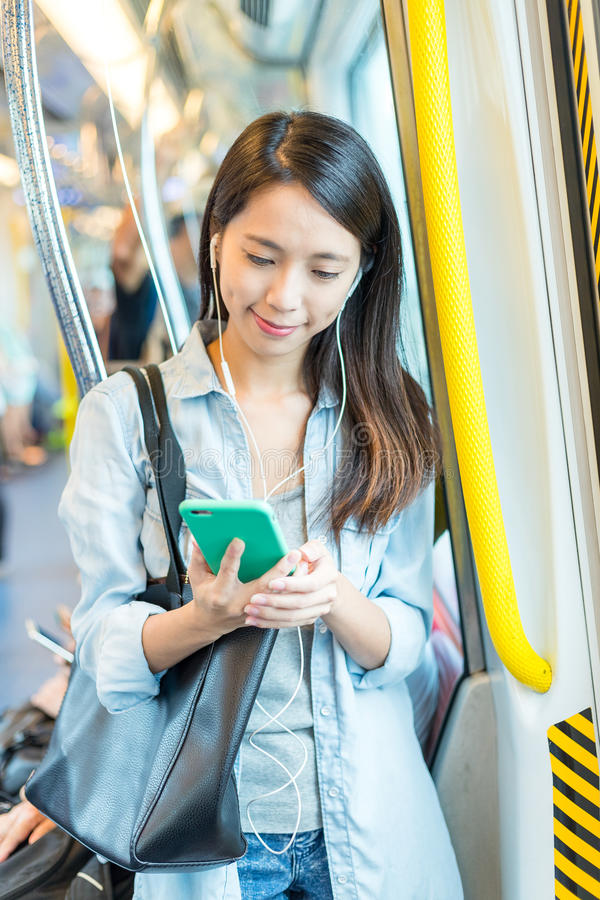 De vrouw luistert aan muziek en het gebruiken van cellphone op trein stock foto