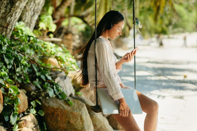 De vrouw luistert aan muziek op strand en holdingslaptop stock foto's