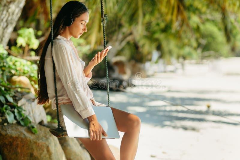 De vrouw luistert aan muziek op strand en holdingslaptop stock afbeelding