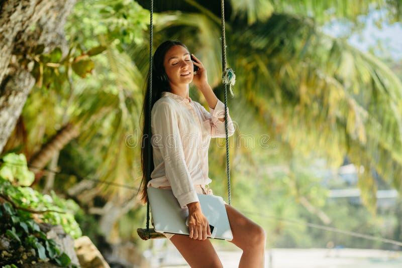 De vrouw luistert aan muziek op strand en holdingslaptop royalty-vrije stock afbeeldingen