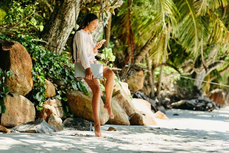 De vrouw luistert aan muziek op strand en holdingslaptop royalty-vrije stock foto