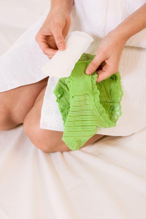 De vrouw maakt damesslipjevoeringen aan haar ondergoed vast stock foto's