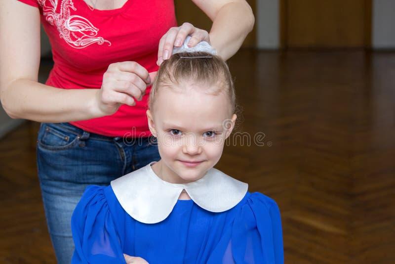 De vrouw maakt een meisjeskapsel voor prestaties stock afbeelding