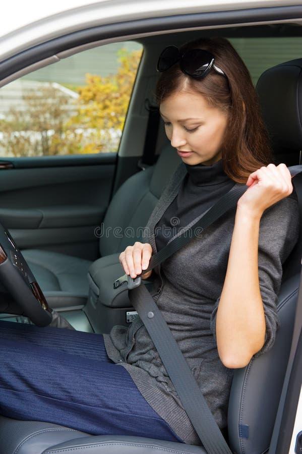 De vrouw maakt een veiligheidsgordel in de auto vast royalty-vrije stock afbeelding