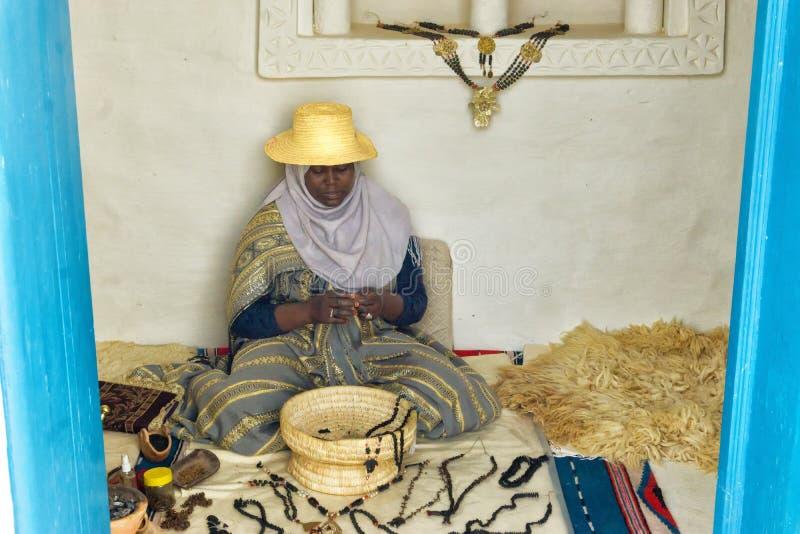 De vrouw maakt neckaces langs Djerba, Tunesië indienen stock fotografie