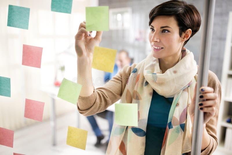 De vrouw maakt regeling op kleverige nota's over glasraad stock foto's