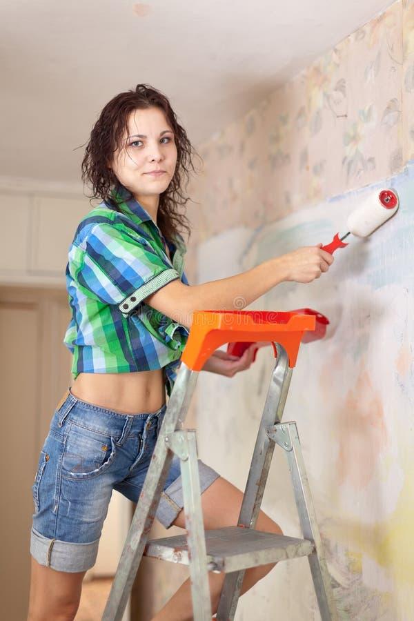 De vrouw maakt reparaties in flat stock foto's