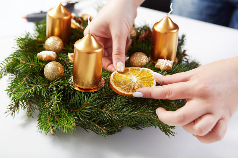 De vrouw maakt sinaasappel op Kerstmiskroon vast stock afbeeldingen