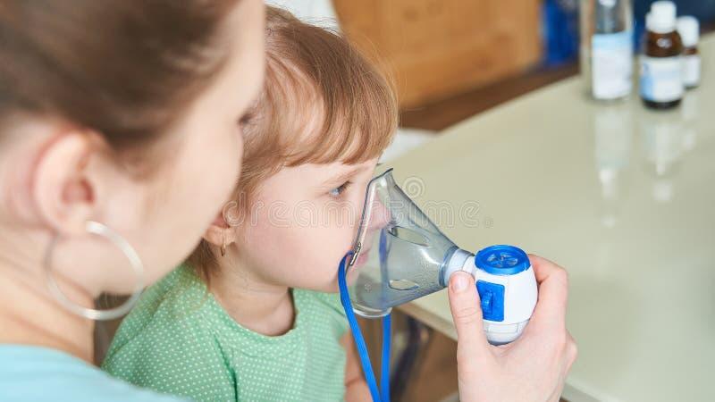 De vrouw maakt tot inhalatie thuis aan een kind brengt het verstuiversmasker aan zijn gezicht inhaleert de damp van het medicijn  stock afbeelding