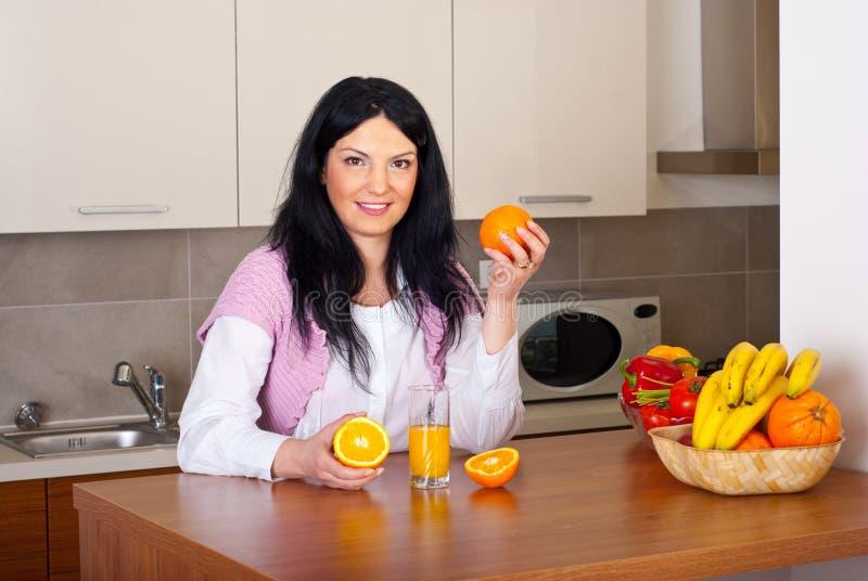 De vrouw maakt vers jus d'orange stock fotografie