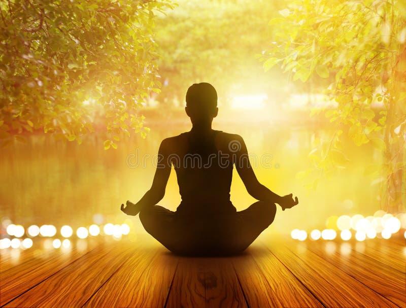 De vrouw mediteerde in zonsopgang en stralen van licht op park en aard royalty-vrije stock foto's