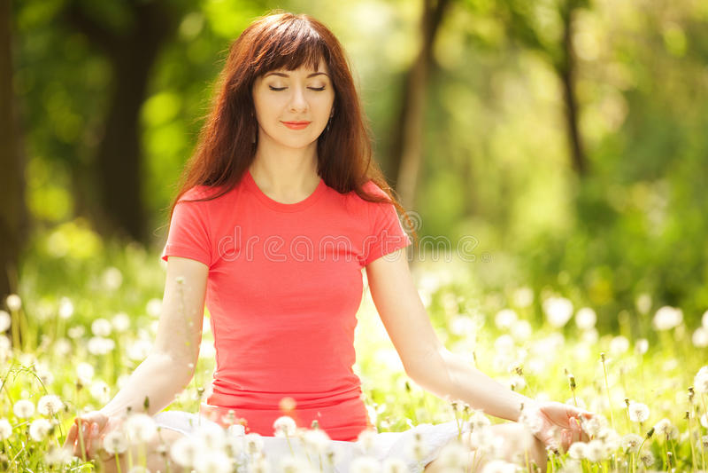 De vrouw mediteert in het park royalty-vrije stock afbeeldingen