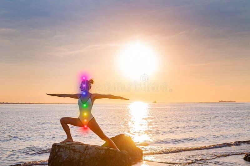 De vrouw mediteert met het gloeien zeven chakras op het strand Het silhouet van vrouw oefent yoga bij zonsondergang op steen uit royalty-vrije stock afbeeldingen