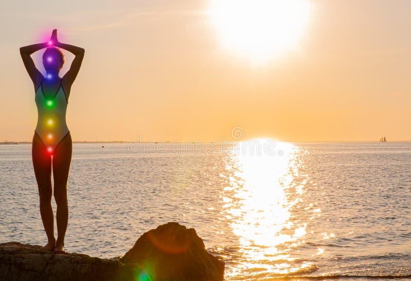 De vrouw mediteert met het gloeien zeven chakras op het strand Het silhouet van vrouw oefent yoga bij zonsondergang uit royalty-vrije stock afbeelding