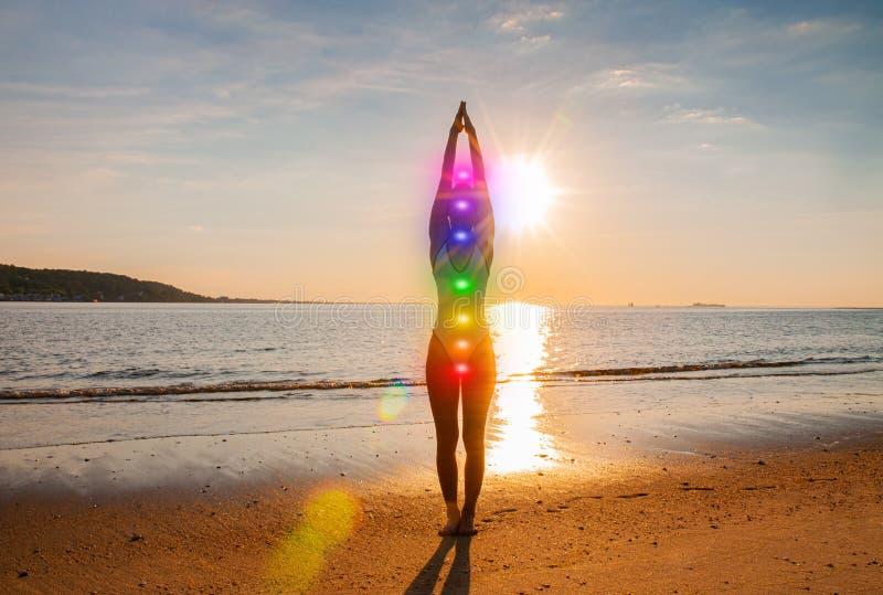 De vrouw mediteert met het gloeien zeven chakras op het strand Het silhouet van vrouw oefent yoga bij zonsondergang uit stock foto