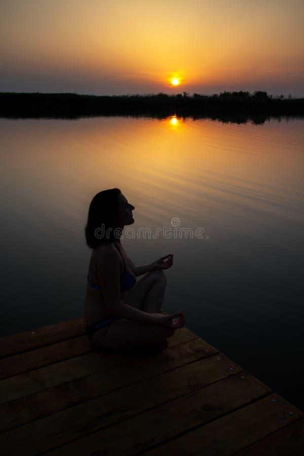 De vrouw mediteert in zonsondergang op het houten dok stock afbeelding