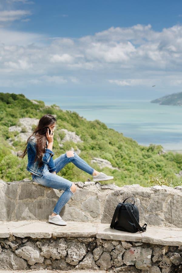 De vrouw met cellphone ontspant in bergen royalty-vrije stock afbeelding