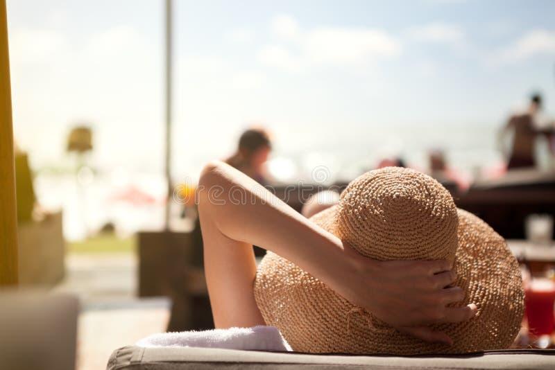 De vrouw met de zomerhoed geniet van in zon royalty-vrije stock fotografie