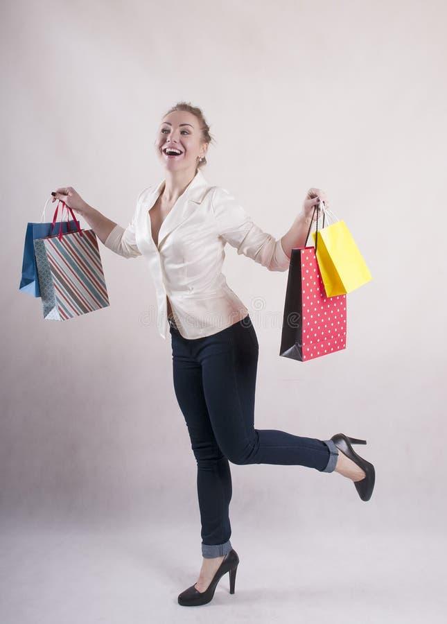 De vrouw met een jasje schokte geschokte aankooppakketten voor aankopenstudio stock afbeeldingen