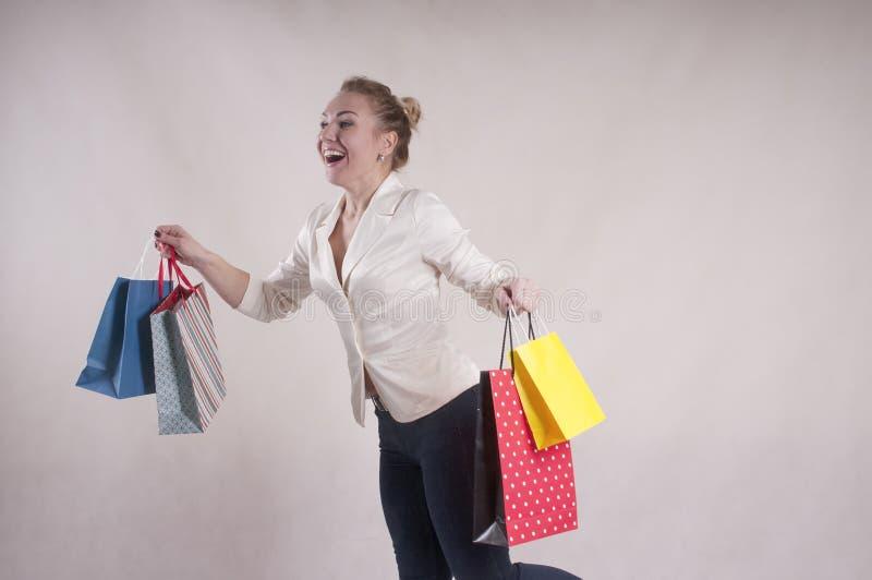 De vrouw met een jasje schokte geschokte pakketten voor aankopenstudio royalty-vrije stock foto
