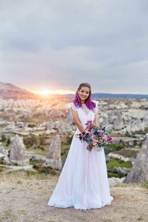 De vrouw met een mooi boeket van bloemen in haar handen bevindt zich op de berg in de stralen van de dageraadzonsondergang Mooi l stock foto