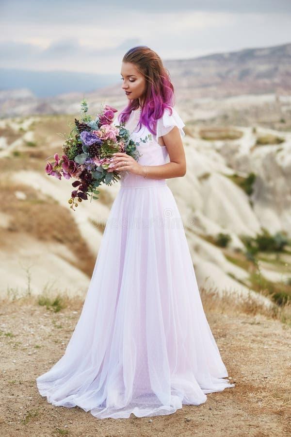 De vrouw met een mooi boeket van bloemen in haar handen bevindt zich op de berg in de stralen van de dageraadzonsondergang Mooi l stock afbeelding