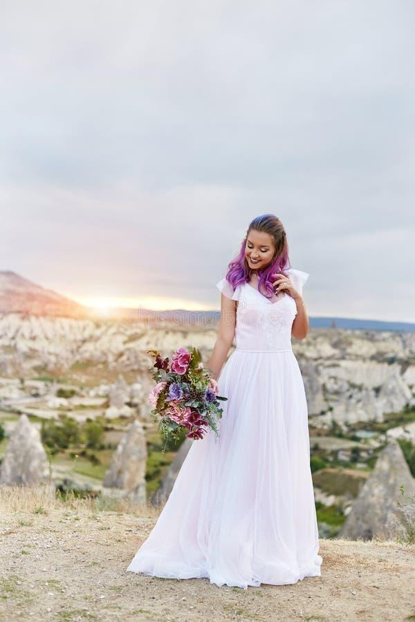 De vrouw met een mooi boeket van bloemen in haar handen bevindt zich op de berg in de stralen van de dageraadzonsondergang Mooi l royalty-vrije stock foto's