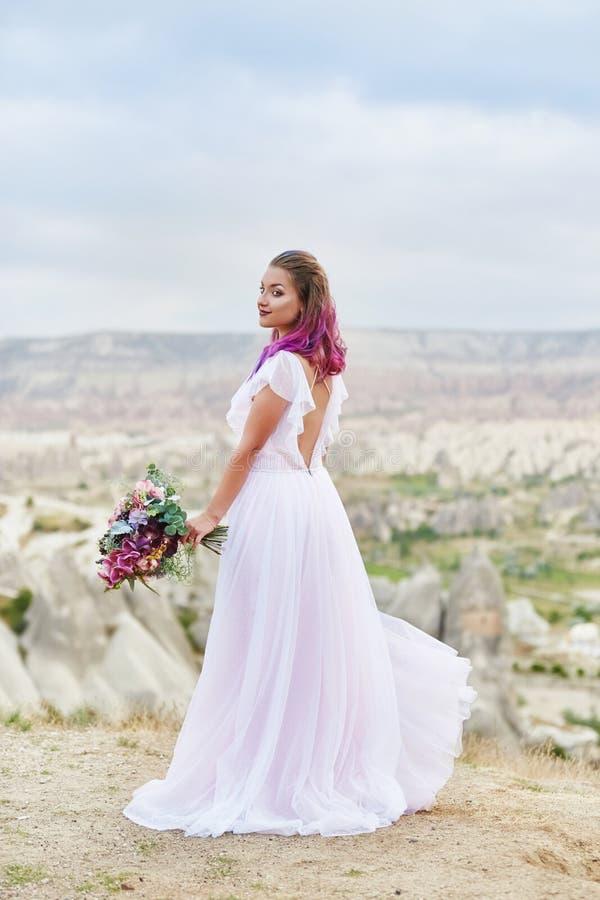 De vrouw met een mooi boeket van bloemen in haar handen bevindt zich op de berg in de stralen van de dageraadzonsondergang Mooi l royalty-vrije stock afbeelding