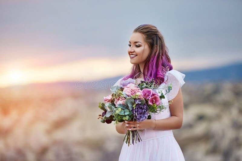 De vrouw met een mooi boeket van bloemen in haar handen bevindt zich op de berg in de stralen van de dageraadzonsondergang Mooi l royalty-vrije stock afbeeldingen
