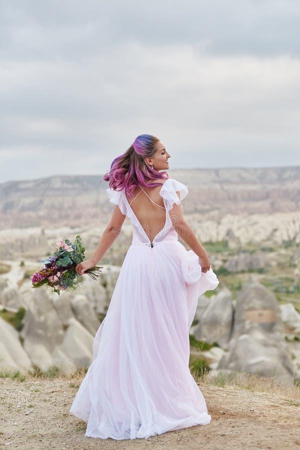 De vrouw met een mooi boeket van bloemen in haar handen danst op de berg in de stralen van de dageraadzonsondergang Mooi lang wit stock foto