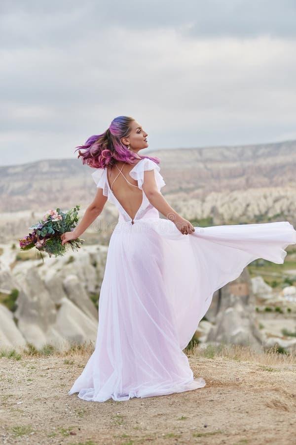De vrouw met een mooi boeket van bloemen in haar handen danst op de berg in de stralen van de dageraadzonsondergang Mooi lang wit royalty-vrije stock fotografie