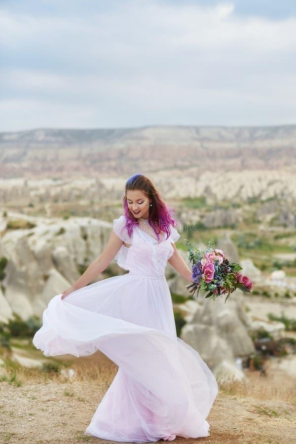 De vrouw met een mooi boeket van bloemen in haar handen danst op de berg in de stralen van de dageraadzonsondergang Mooi lang wit royalty-vrije stock foto