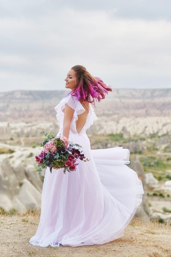 De vrouw met een mooi boeket van bloemen in haar handen danst op de berg in de stralen van de dageraadzonsondergang Mooi lang wit stock afbeelding