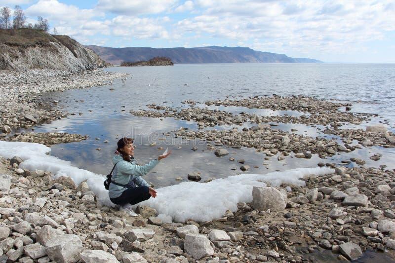 De vrouw met een reepje van ijs in een hand bij Meer Baikal royalty-vrije stock afbeelding