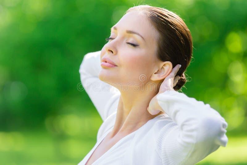 De vrouw met gesloten ogen zet handen achter hoofd royalty-vrije stock afbeelding