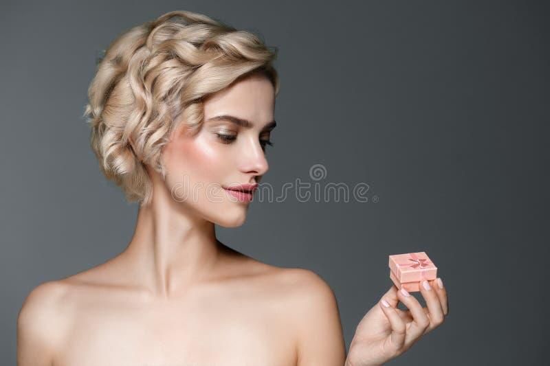 De vrouw met giftdoos overhandigt binnen grijze achtergrond royalty-vrije stock afbeelding