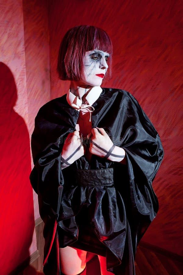 De vrouw met gotisch maakt omhoog in zwarte mantel agains royalty-vrije stock foto's