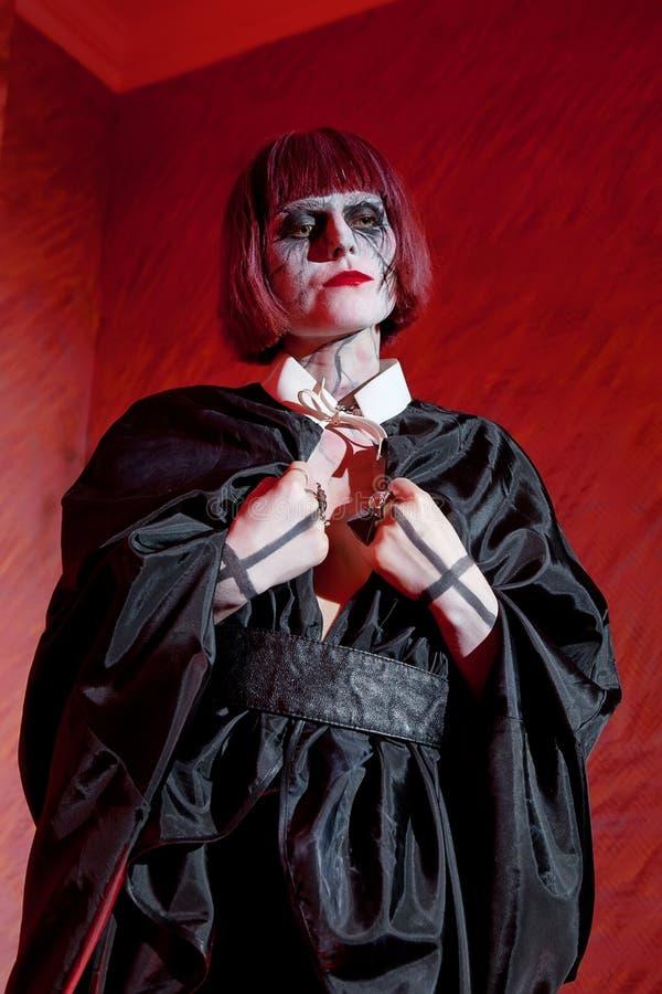 De vrouw met gotisch maakt omhoog in zwarte mantel agains stock afbeelding