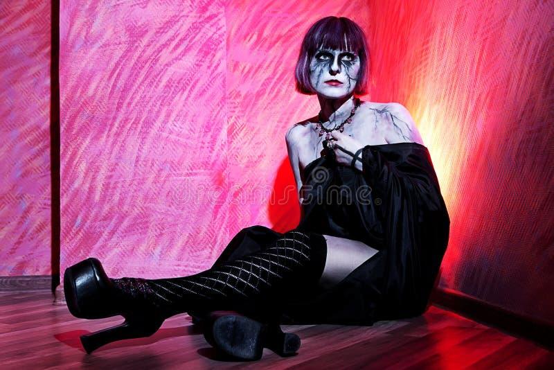 De vrouw met gotisch maakt omhoog in zwarte mantel agains stock foto's