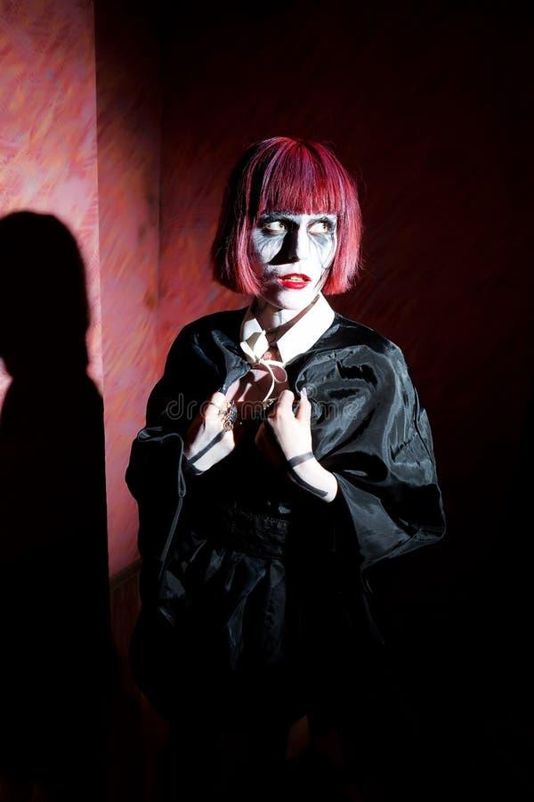 De vrouw met gotisch maakt omhoog in zwarte mantel agains stock foto