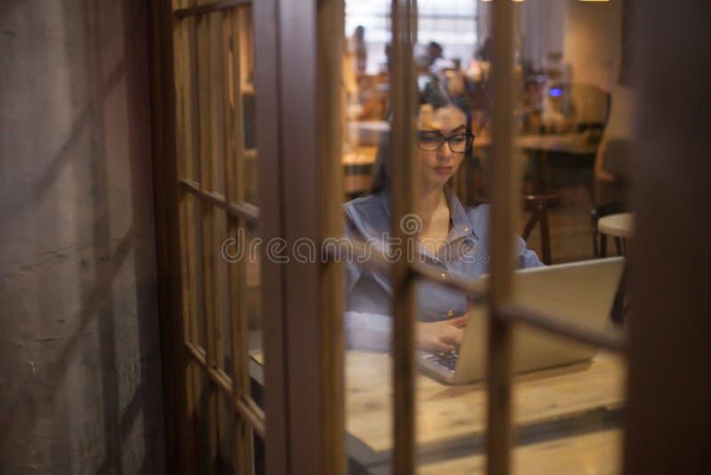 De vrouw met grijze laptop wordt gelet op royalty-vrije stock afbeeldingen