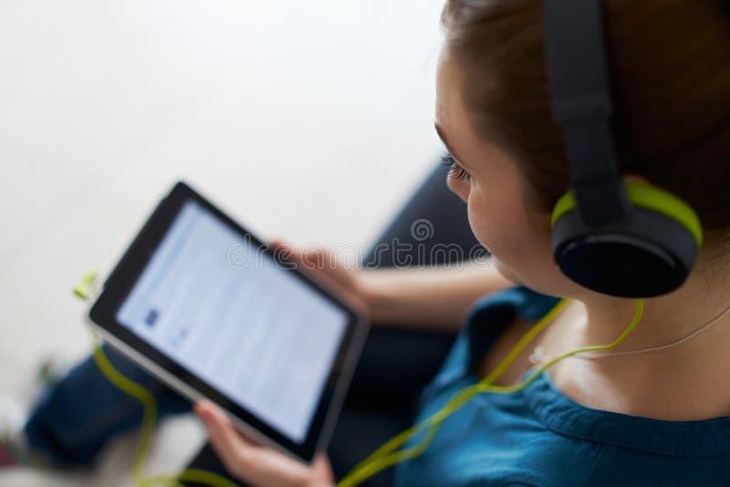 De vrouw met Groene Hoofdtelefoons luistert Podcast-PC van de Muziektablet stock foto