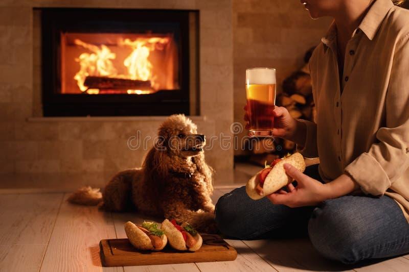 De vrouw met haar hond zit bij de vloer en het eten van hotdog royalty-vrije stock afbeelding