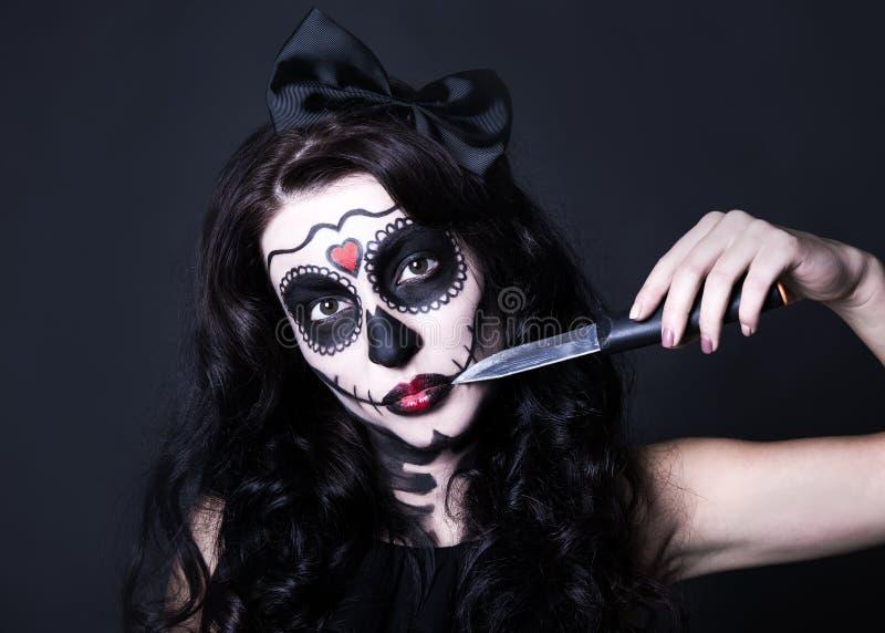 De vrouw met Halloween-schedel maakt omhoog het snijden van haar gezicht met mes o stock foto