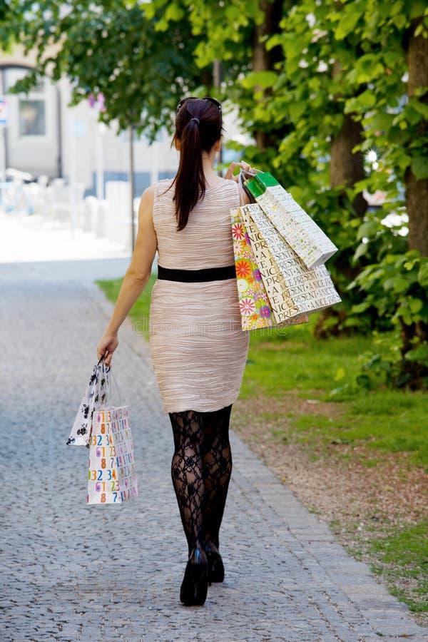 De vrouw met het winkelen doet terwijl het winkelen in zakken royalty-vrije stock afbeeldingen