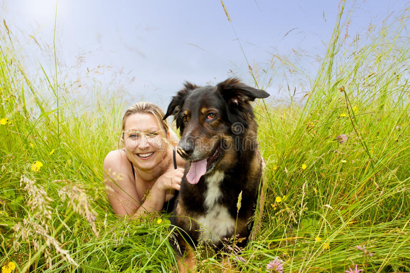 De vrouw met hond ligt op gras stock foto