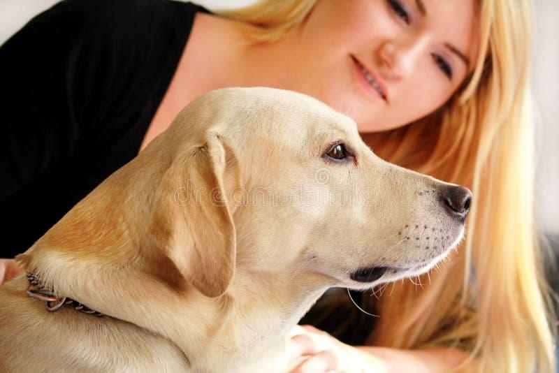 De vrouw met hond rust thuis in bed, ontspannend in slaapkamer Het meisje petting met haar hond Portret van leuk geel Labrador stock afbeelding