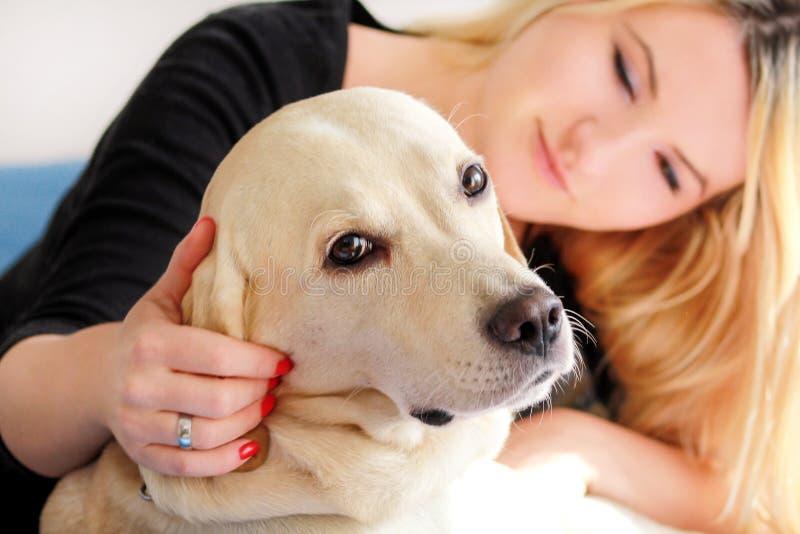 De vrouw met hond rust thuis in bed, ontspannend in slaapkamer Het meisje petting met haar hond Portret van leuk geel Labrador stock afbeeldingen